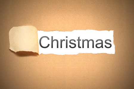reveal: brown packaging paper torn to reveal christmas