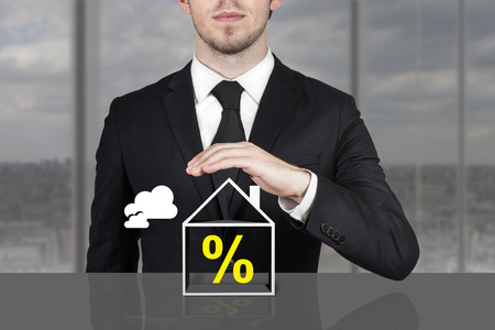 immobile: businessman in office holding protective hand above building percentage symbol Stock Photo