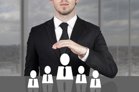 businessman in black suit holding protective hand above employee staff