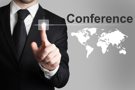 worldmap: businessman in black suit pushing button conference international worldmap Stock Photo