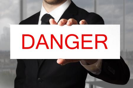 mortal danger: businessman in black suit holding sign danger