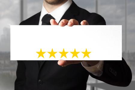 businessman in black suit holding sign five golden stars photo