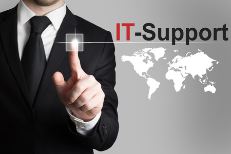 specialists: businessman in black suit pushing button it support international worldmap