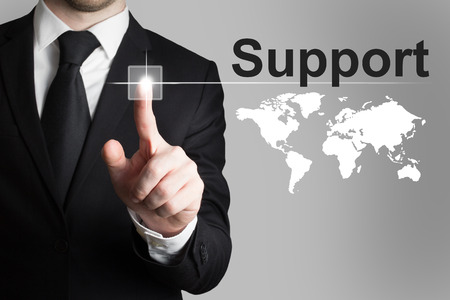 businessman in suit pushing button support worldmap international Banque d'images