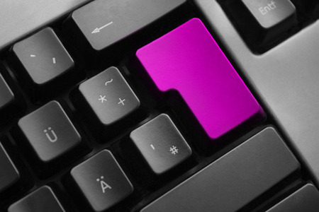 personal data privacy issues: dark grey keyboard with purple colored enter button Stock Photo