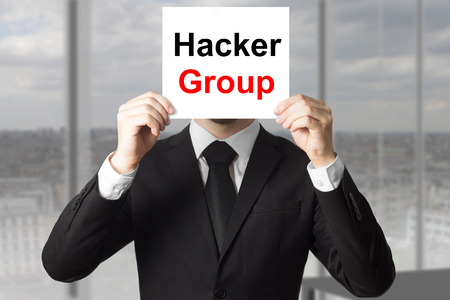 cyberwar: businessman in office hiding face behind sign hacker group