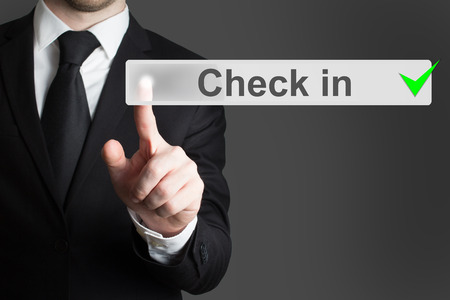 internet terminals: businessman in black suit pressing button check in Stock Photo