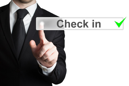 pushing button: businessman in black suit pushing button check in isolated Stock Photo