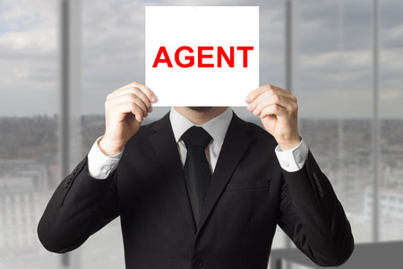 undercover agent: secret agent in black suit hiding face behind sign undercover Stock Photo