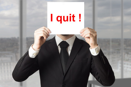 businessman in office hiding face behind sign i quit