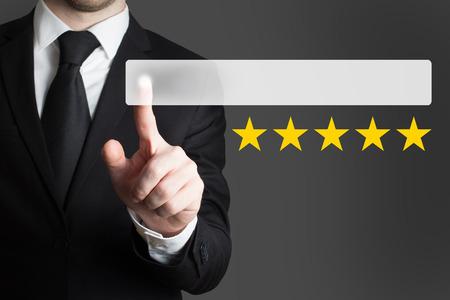 proved: Uomo d'affari in tuta che spinge il tasto cinque stelle di valutazione