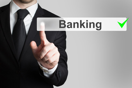 international bank account number: businessman in black suit pushing button banking