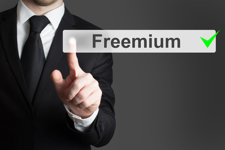 downloadable: businessman in black suit pushing flat button freemium green checked Stock Photo