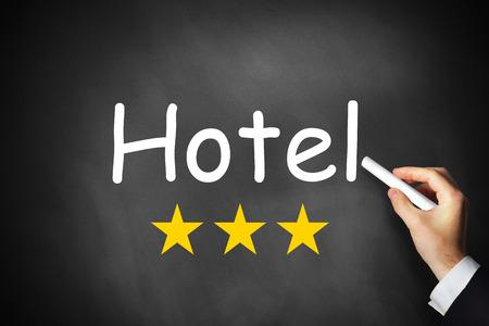 hand writing hotel on black chalkboard three rating stars