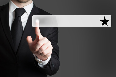 pushing button: businessman in suit pushing button black star Stock Photo