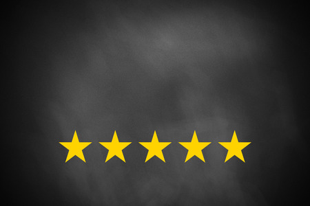 five golden rating stars on black chalkboard