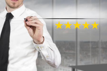 five stars: businessman in office writing five golden stars premium