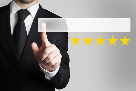proved: businessman in black suit pushing flat button five rating stars Stock Photo