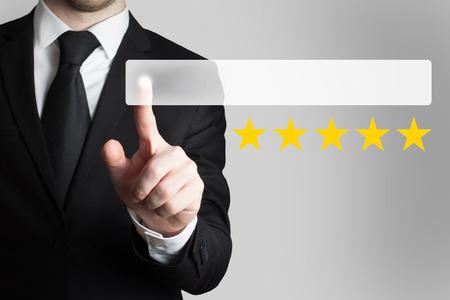 businessman in black suit pushing flat button five rating stars Standard-Bild