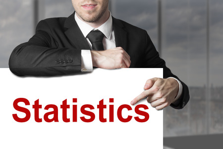 penniless: businessman in office pointing on sign statistics