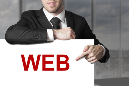 businessman in black suit pointing on sign web