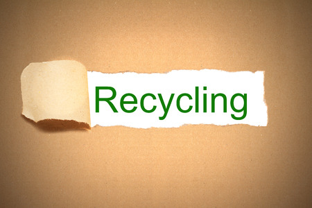 reveal: brown packaging paper torn to reveal recycling