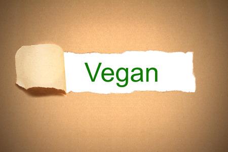 reveal: brown packaging paper torn to reveal vegan Stock Photo