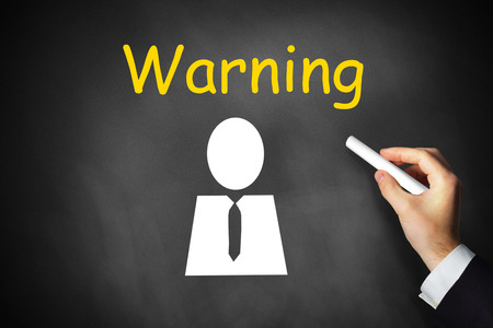 stay alert: businessmans hand writing warning on black chalkboard