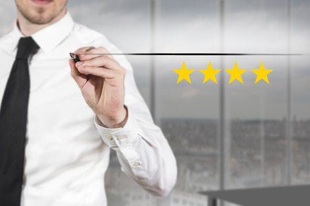 businessman in office pushing flat button four golden rating stars