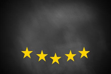 five golden rating stars on black chalkboard