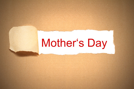 reveal: brown packaging paper torn to reveal mothers day Stock Photo