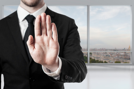 illegally: businessman in office room hand stop gesture