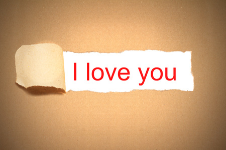reveal: brown paper envelope torn to reveal message i love you