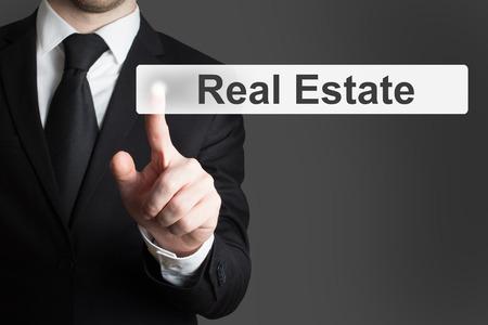 ni�o empujando: hombre de negocios en traje negro empujando bot�n plano inmobiliario