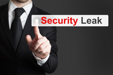 cyberwar: businessman in black suit pushing touchscreen security leak