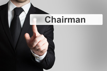 chairman: businessman in black suit pushing button chairman Stock Photo