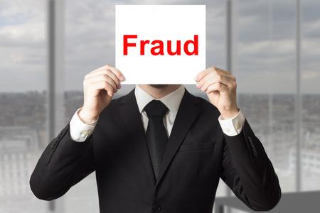 businessman in black suit hiding face fraud