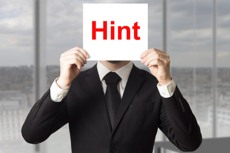 hint: businessman in black suit hiding face behind sign hint