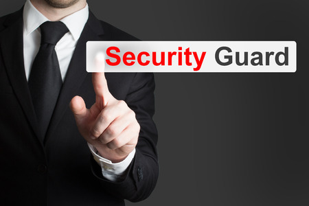 pushing button: businessman in black suit pushing button security guard
