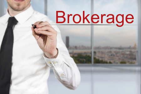 brokerage: businessman in office writing brokerage in the air