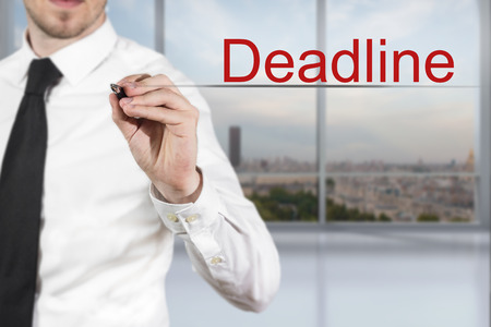 time remaining: businessman in office room writing deadline in the air office