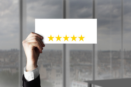 hotel reviews: businessmans hand holding up small sign five rating stars Stock Photo