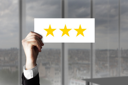hotel reviews: businessmans hand holding up small sign three rating stars Stock Photo