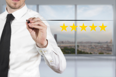 proved: businessman drawing line in the air five golden rating stars Archivio Fotografico