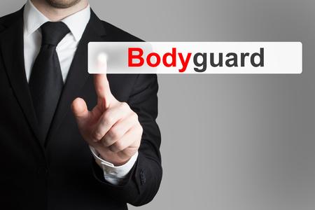 guardaespaldas: hombre de negocios en traje negro empuja el bot�n de guardia Foto de archivo