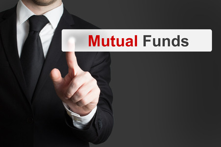 mutual funds: businessman in office pushing touchscreen button mutual funds Stock Photo