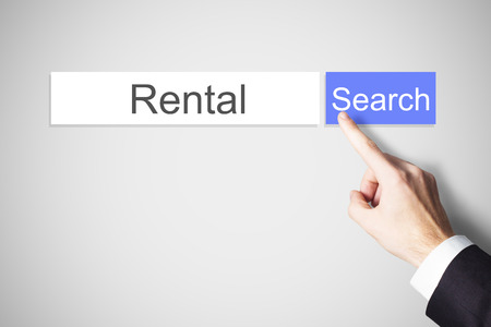 home expenses: businessmans finger pushing blue web search button rental