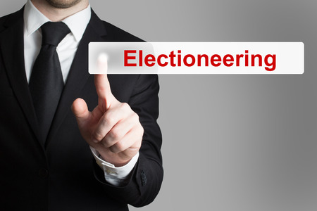 electioneering: businessman in black suit pushing flat touchscreen electioneering