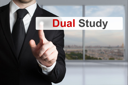 dual: businessman in black suit pushing button dual study