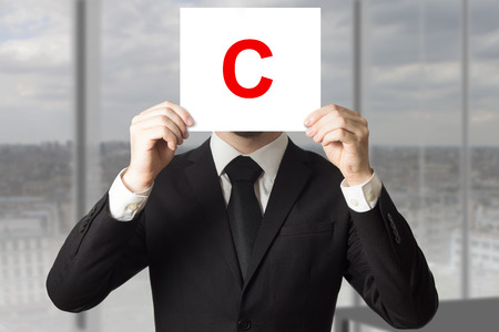 businessman in black suit holding up sign with letter c